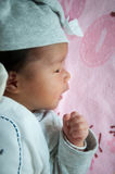 Focus at Asian baby girl with gray hat while sleeping and playing on the bed /  Close up at cute newborn is looking at camera Stock Photos