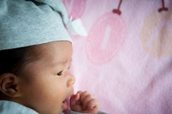 Focus at Asian baby girl with gray hat while sleeping and playing on the bed /  Close up at cute newborn is looking at camera Royalty Free Stock Photos