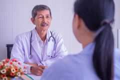 Focus of Asian mature male doctor and female patient sitting talking in hospital. royalty free stock image
