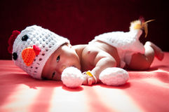 Focus at Asian newborn baby girl with costumes Chicken with two eggs beside the window with sunlight Royalty Free Stock Photography