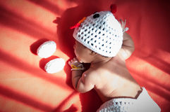 Focus at Asian newborn baby girl with costumes Chicken with two eggs beside the window with sunlight Royalty Free Stock Image