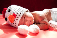 Focus at Asian newborn baby girl with costumes Chicken with two eggs beside the window with sunlight Stock Photos