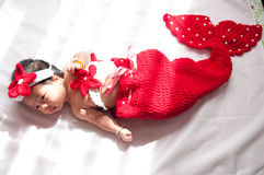 Focus at Asian newborn baby girl with costumes little mermaid in red color beside the window with sunlight Royalty Free Stock Images