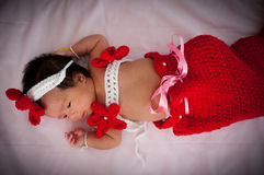 Focus at Asian newborn baby girl with costumes little mermaid in red color beside the window with sunlight Stock Image