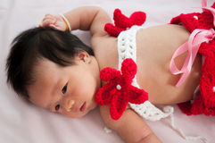 Focus at Asian newborn baby girl with costumes little mermaid in red color beside the window with sunlight Royalty Free Stock Photo