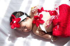 Focus at Asian newborn baby girl with costumes little mermaid in red color beside the window with sunlight Stock Photos