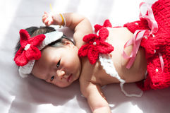 Focus at Asian newborn baby girl with costumes little mermaid in red color beside the window with sunlight Royalty Free Stock Photos