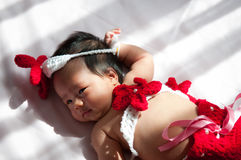 Focus at Asian newborn baby girl with costumes little mermaid in red color beside the window with sunlight Stock Photography