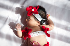 Focus at Asian newborn baby girl with costumes little mermaid in red color beside the window with sunlight Stock Photo