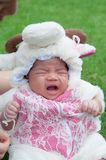 Focus at Asian newborn baby girl with costumes little sheep in the garden and mother is holding her. Royalty Free Stock Photo