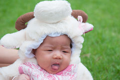 Focus at Asian newborn baby girl with costumes little sheep in the garden and mother is holding her. Royalty Free Stock Image