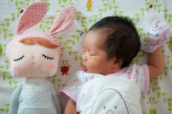 Focus at Baby girl with nice headband while snoozing and playing with cute doll on the bed. Newborn girl is sleep with cute doll. Royalty Free Stock Image