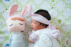 Focus at Baby girl with nice headband while snoozing and playing with cute doll on the bed. Newborn girl is sleep with cute doll. Royalty Free Stock Photo