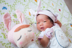 Focus at Baby girl with nice headband while snoozing and playing with cute doll on the bed. Newborn girl is sleep with cute doll. Royalty Free Stock Photography