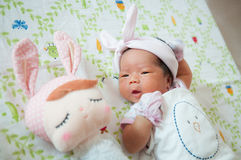 Focus at Baby girl with nice headband while snoozing and playing with cute doll on the bed. Newborn girl is sleep with cute doll. Stock Photo