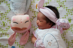 Focus at Baby girl with nice headband while snoozing and playing with cute doll on the bed. Newborn girl is sleep with cute doll. Stock Images