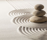 Focus on balancing stones in sand for progression. Zen stillness and wellness with sand and stones garden Stock Photo