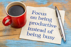 Focus on being productive instead busy. Focus on being productive instead of being busy - handwriting on a napkin with a cup of espresso coffee Stock Photo