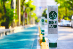Focus bike lane sign pole in with green tree background. Focus bike lane sign pole in with blur green tree background Stock Photos
