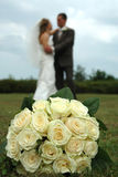 Focus and blur. Bouquet is in focus. The wedding couple are in blur Royalty Free Stock Photos