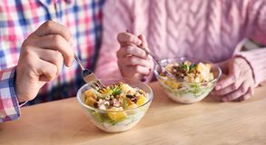 Focus on bowl with dessert useful light fruit salad. Concept of family healthy lifestyle and diet. Blurred background. royalty free stock image