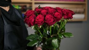 Focus on the bunch of red roses: young attractive female florist arranging bouquet of beautiful red roses at flower shop