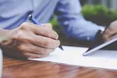 Focus on businessman hand. Businessman writing document in stree. T cafe Stock Photography