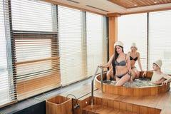 Group of caucasian diverse friends enjoying jacuzzi in hotel spa. Focus on caucasian slim women in bikini leaving friends in wooden round bath, modern bathroom stock photo