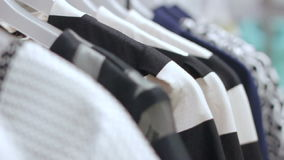 Focus Changes from Beginning Hangers Line with Dresses to End. Focus changes from beginning hangers line with black and white dresses with different patterns to stock footage