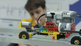 Focus Changes from Lego Blocks Robot to Teenager. KAZAN, TATARSTAN/RUSSIA - JUNE 03 2015: Focus changes from driving on rail Lego blocks robot to concentrated stock video footage