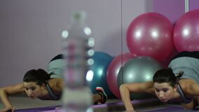 Focus changing from flexible woman stretching in gym to bottle of fresh water. Stock footage stock footage