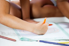 Focus on child hand holding the crayon is  painting her picture Royalty Free Stock Photo