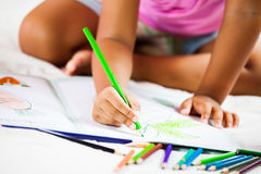 Focus on child hand holding the crayon is  painting her picture Royalty Free Stock Photography