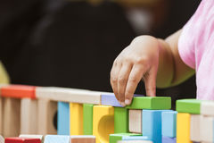 Focus on child`s hand  playing with colorful wooden blocks Royalty Free Stock Photography