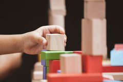 Focus on child`s hand  playing with colorful wooden blocks Stock Images