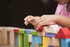 Focus on child`s hand  playing with colorful wooden blocks Royalty Free Stock Photos