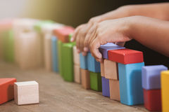 Focus on child`s hand  playing with colorful wooden blocks Royalty Free Stock Photo