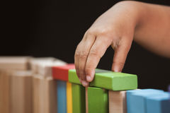 Focus on child`s hand  playing with colorful wooden blocks Stock Photography