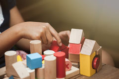Focus on child`s hand  playing with colorful wooden blocks Royalty Free Stock Image