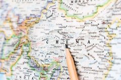 Focus on CHINA on the world map with pencil pointing.  royalty free stock photo