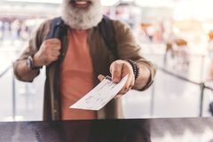 Old man arm holding out card. Focus on close up pensioner hand giving ticket to booking office. Unshaven retire expressing happiness. Focus on document Stock Photos