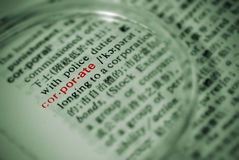 Focus on corporate. With magnifier in book in green color stock photo