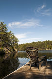 Focus on Cottage Chair. Holiday at the cottage with the sunlight hitting the chair on the dock with lake and shoreline in the background Stock Photography