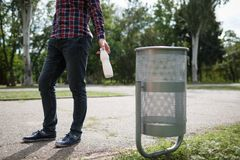 Litttering male. An empty of plastic drinking bottle littering on the road floor. Concept of environmental protection. Focus on cover of a paper cup the bottom Stock Photos