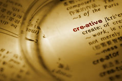 Focus on creative. With magnifier on book stock image