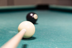Focus on cue aiming black ball into snooker billards pocket. Focus on cue aiming black ball into snooker pool billards table pocket Royalty Free Stock Photos