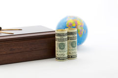 Focus on currency and wood box with globe in background Royalty Free Stock Image