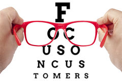 Focus Customer Customers Spectacles Concept. Red spectacles focusing on text focus on customers arranged as eye chart test. Letters outside field of view are Royalty Free Stock Photography