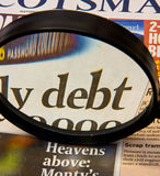 Focus on debt headline. An image of the word debt viewed through a large magnifier.  This is a concept image reflecting world wide concern about countries and Royalty Free Stock Images