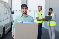 Focus of delivery man is holding a cardboard box and smiling to the camera. Focus of delivery men is holding a cardboard box and smiling to the camera in a Stock Photo